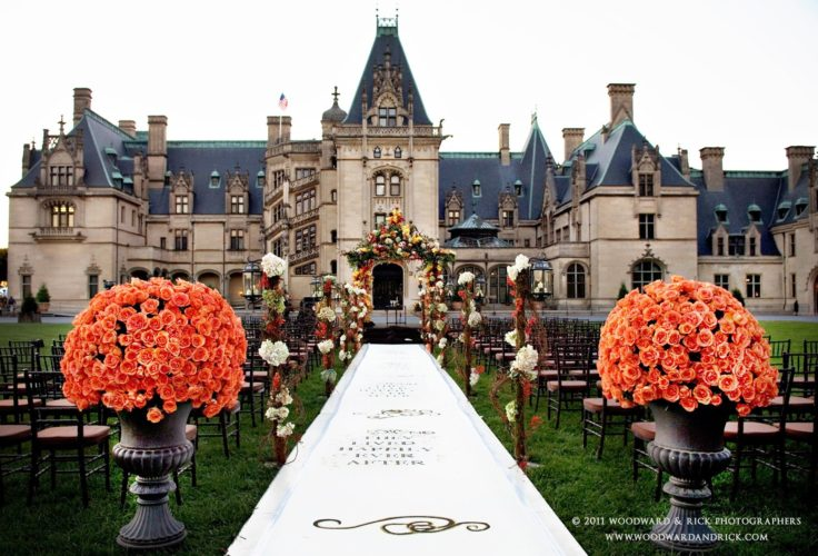 The Biltmore estate front yard of a wedding isle with orange flowers and mansion in north carolina