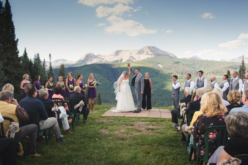Mountaintop destination wedding with guests and view of mountains and sky