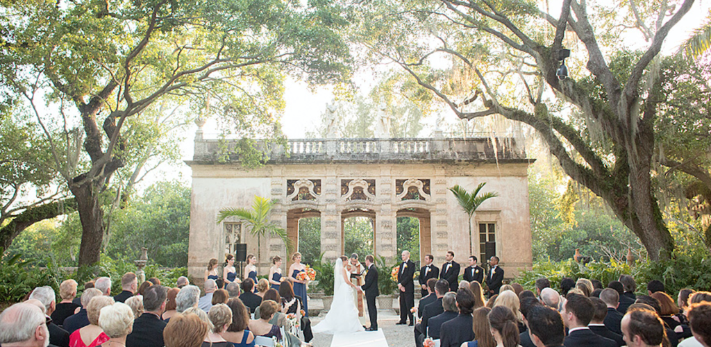 wedding in progress at viscaya museum in Miami with big trees and guests