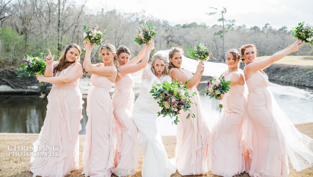 bridesmaids in a fun stance with bride in middle and green bouquet in front of a lake