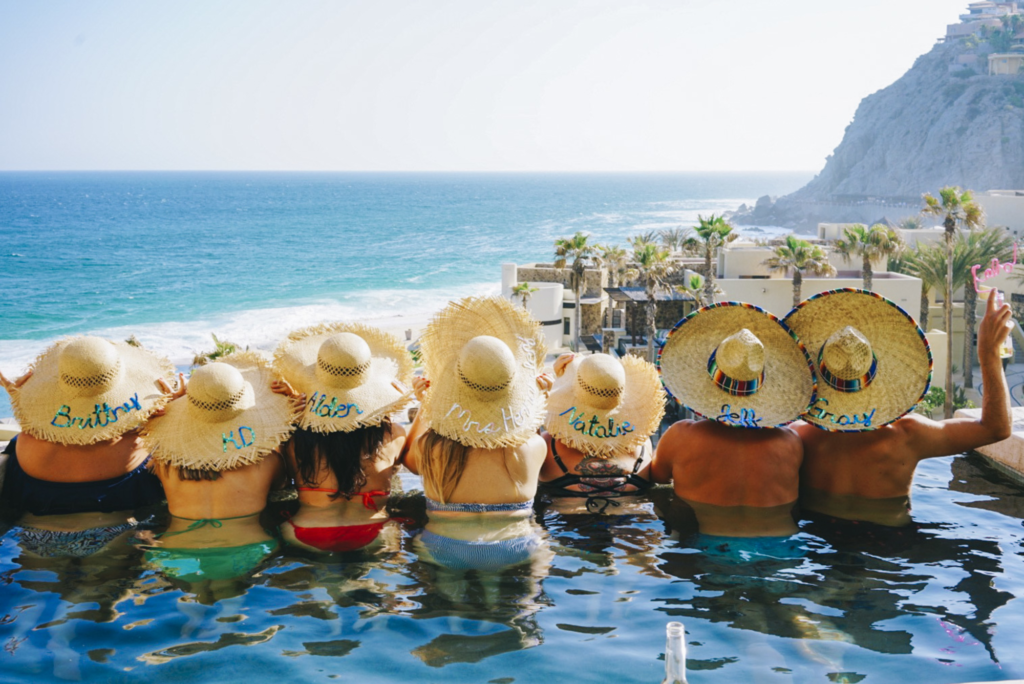 Bachelorette destination party with hats in pool at a tropical mountain and ocean paradise